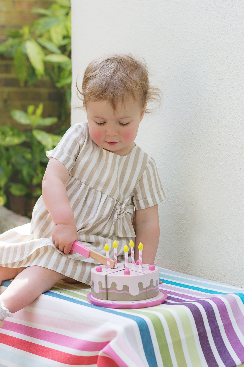 A little girl sits on her own playing with her pretend wooden cake and candles