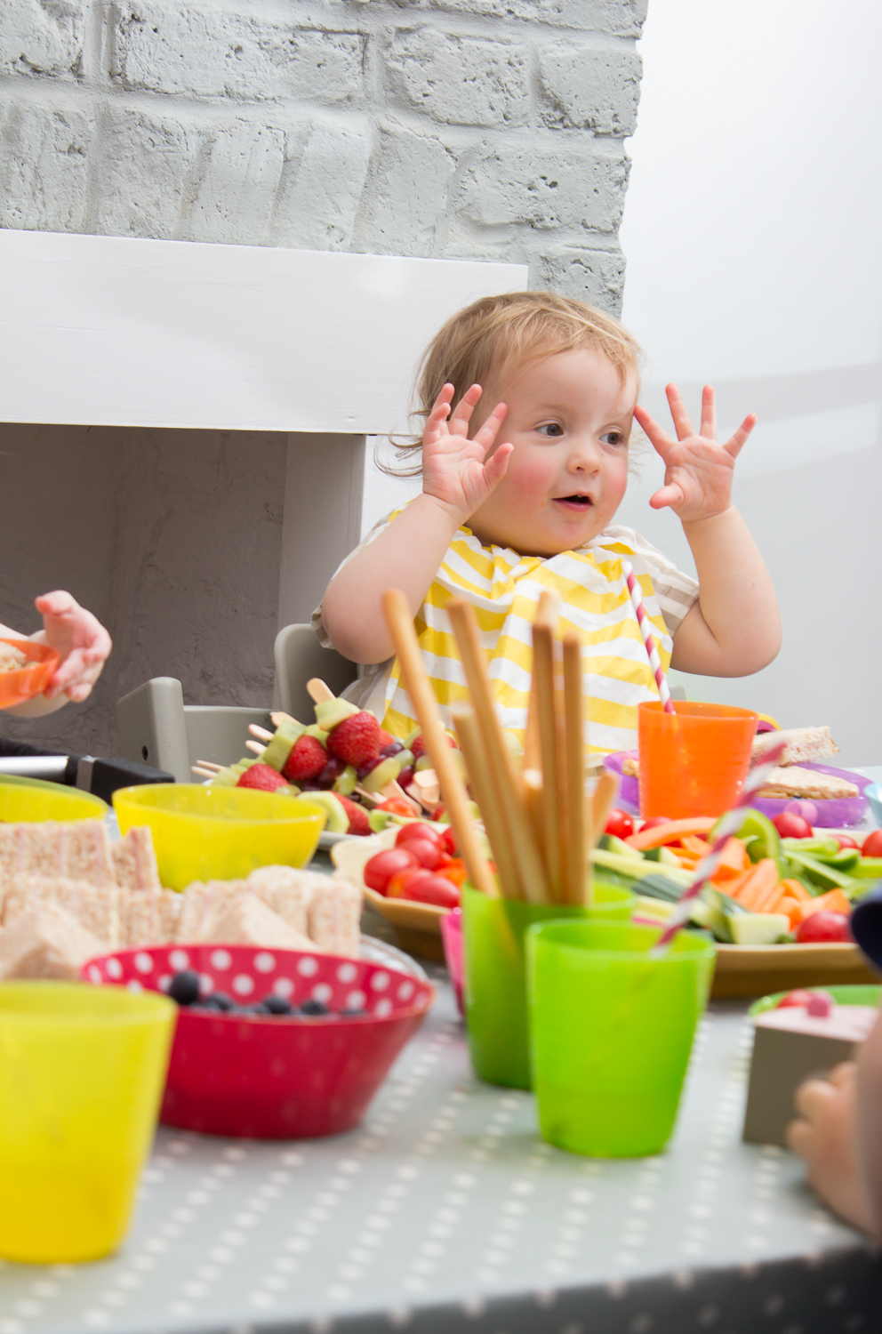 A little girl sits at a table filled with party food showing ten fingers in the air