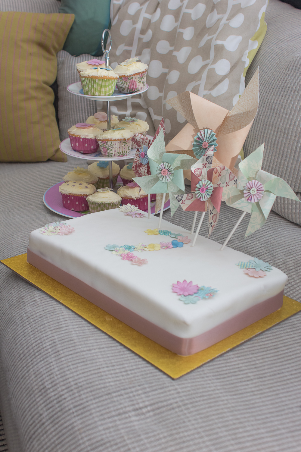 A child's second birthday cake - it's white with the number two decorated on in little edible flowers, with handmaid windmills along the top