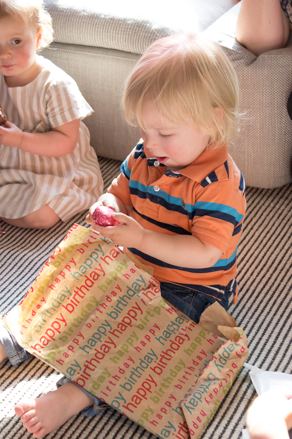 A little boy in a striped orange t-shirt opens a layer of wrapping paper during parce-the-parcel