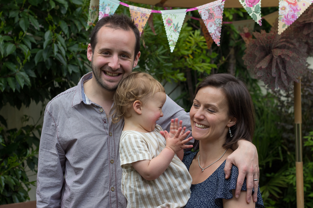 A mum, dad and their birthday girl pose for a family photograph in their garden in Tunbridge Wells - the little girl is giggling and distracting her Mum