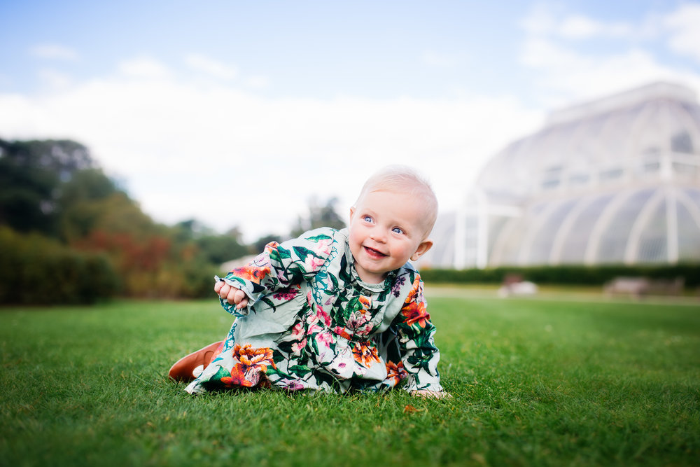 Baby girl on grass smiling by Susie Fisher Photography in Woking