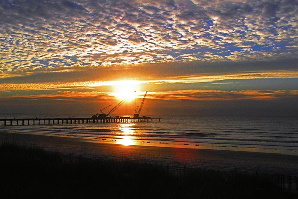 "Sunrise Over The Pier"" was taken in North Myrtle Beach, SC, during a magical vacation our family took in Mid-December one year. I am usually an early riser, and was already awake at 6 AM when the sun started to climb through the cloudbank. Reflections and diffused light are my friends."