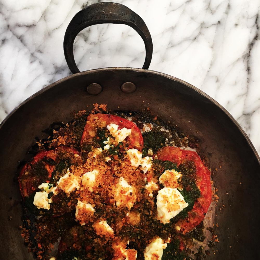 Stoneburner's baked beefsteak tomatoes, with lovage,feta, and anchovy breadcrumbs in one of our gratin pans.