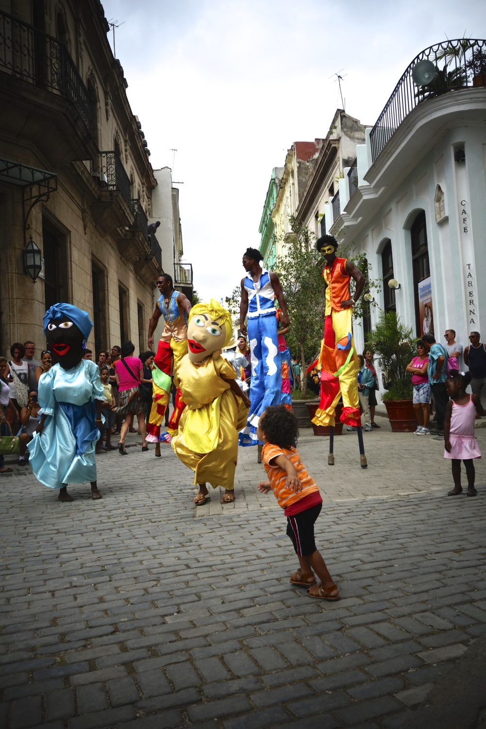 Neighborhood children come out to dance alongside an afternoon street performance.