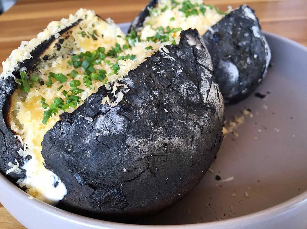 A side of potatoes baked in the coals and topped with creme fraiche, aged Gouda, and chives. Photo by Charcoal Venice