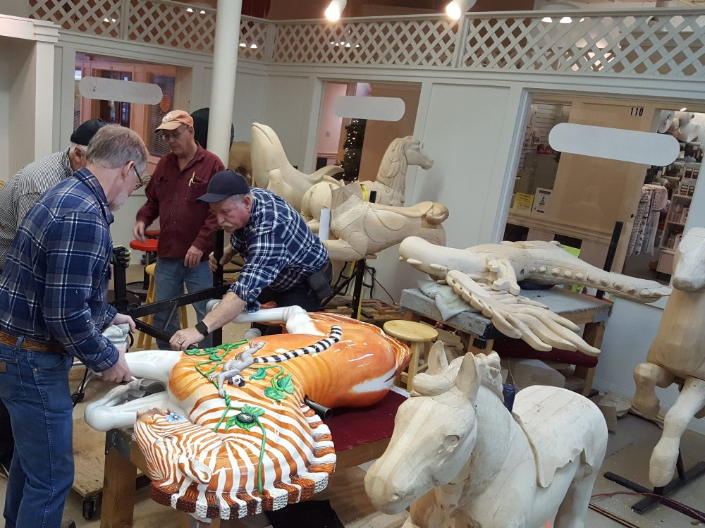 From the Albany, Oregon Carousel carving studio: volunteers fitting Quigga the Quagga for stirrups. ( Photo by Robin Murez )