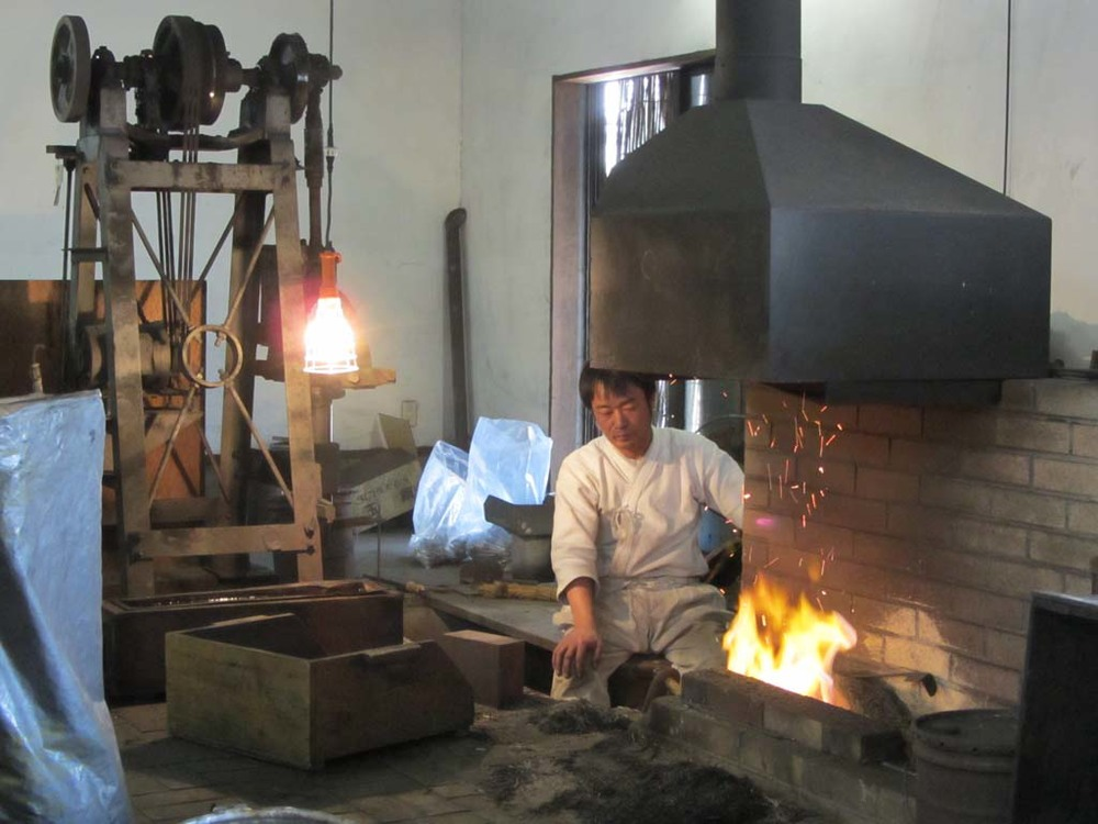 A blacksmith at work in front of the forge at the museum.