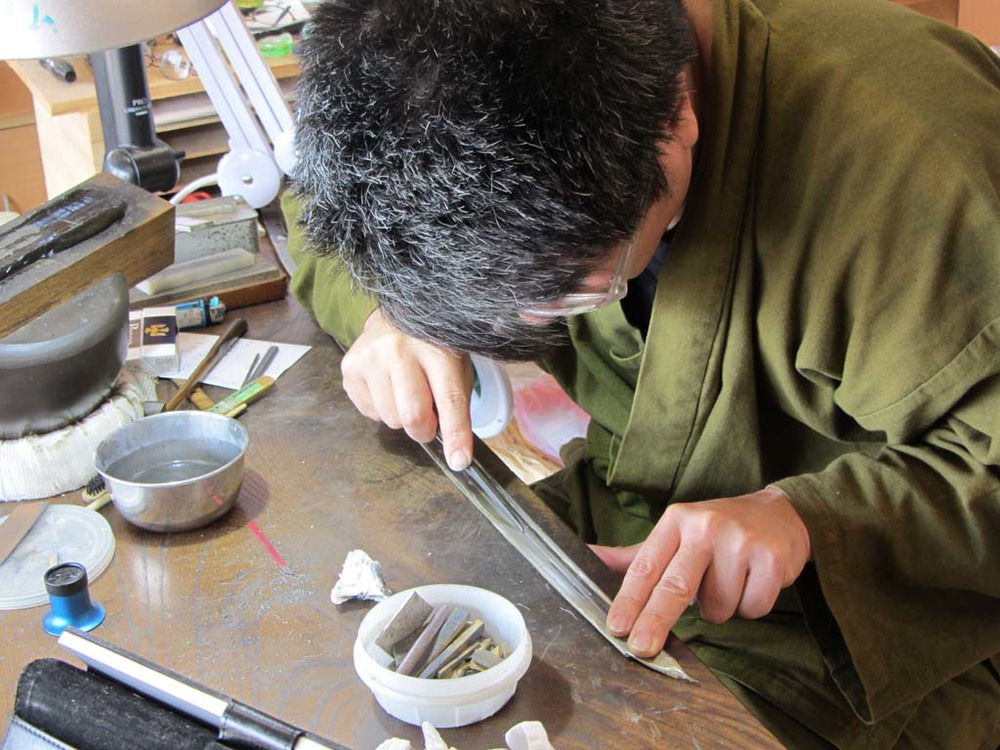 A craftsman repairing an antique sword.