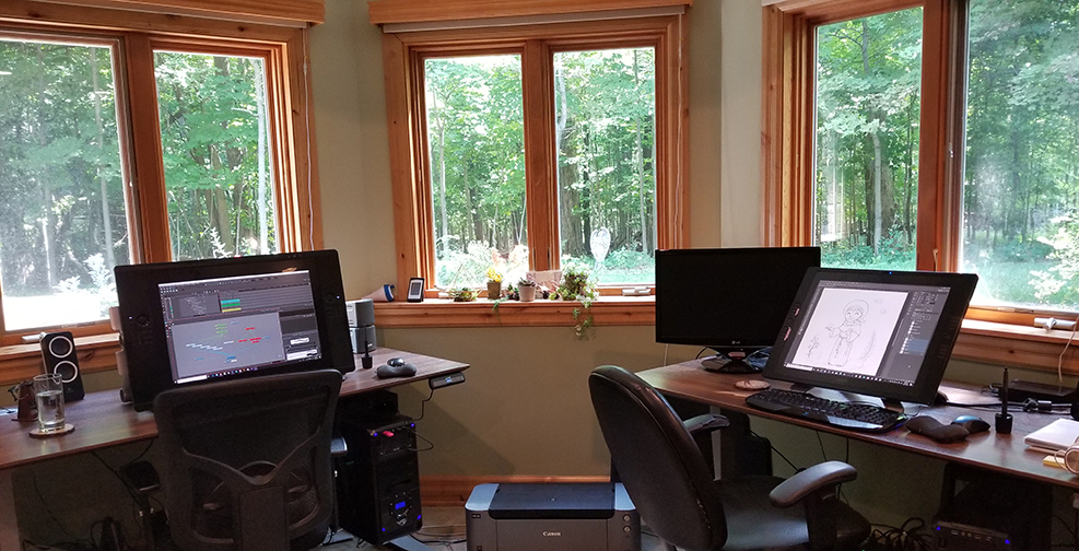 The home studio has a tranquil view and is equipped with standing desks and Cintqs.