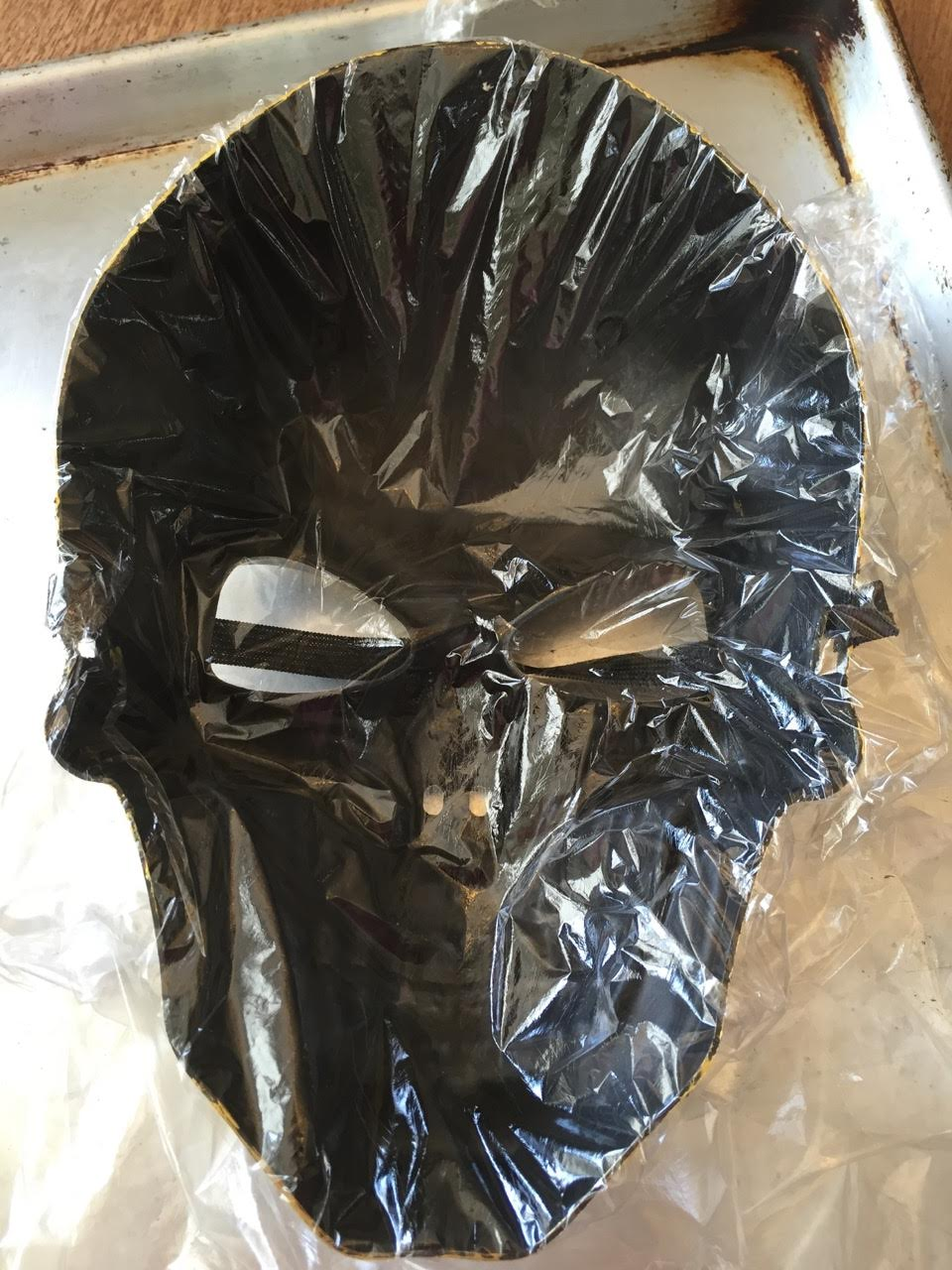Line a clean Halloween mask with plastic wrap. Pros wrap down into all crevices and make sure wrap extends beyond mask.