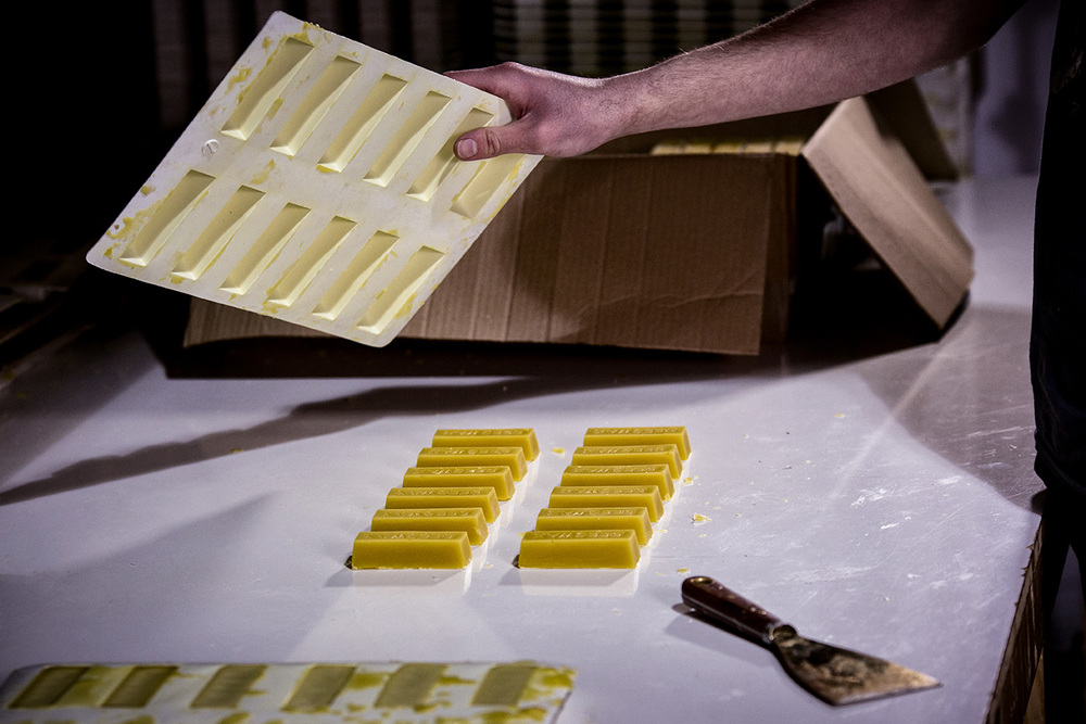 3.  The hot beeswax is left to set, turned upside down and gently tapped to remove the sticks
