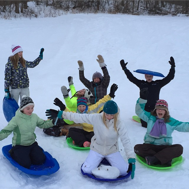 Show me your downhill sledding face!! Young Women in the Woods go sledding. #redwingelc #sledding #minnesotawinter #outdoorwomen