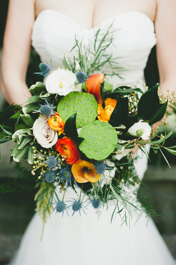 Lotus Pod & Thistle Bouquet Ingredients: ranunculus, calla lilies, blue thistle, lotus pods, olive branch, sweetheart roses, lisisanthus, camellia leaves, amaranthus,  plumosa, cotton and pittosporum.