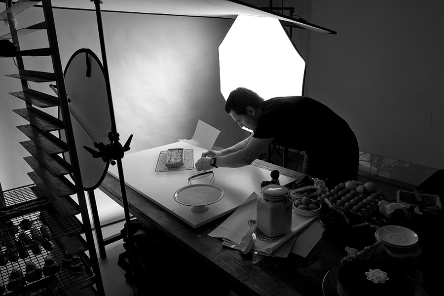 Peter Pattison styling the food in a coolroom  where the photoshoot was taking place