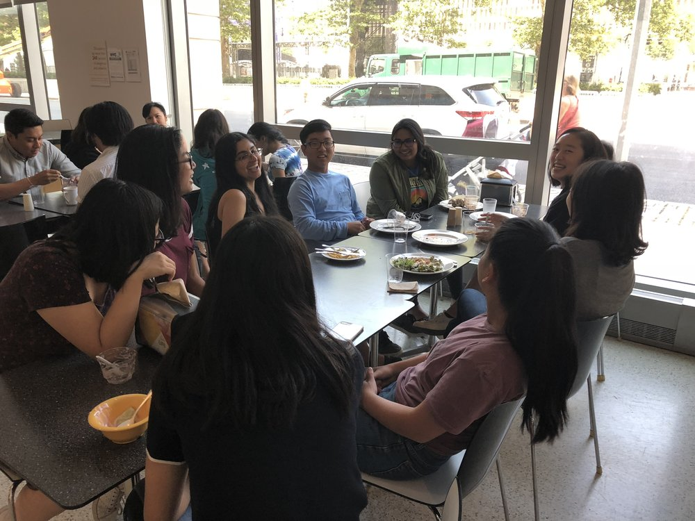 Students having lunch with Tara Hariharan, head of research at NWI Management LP.