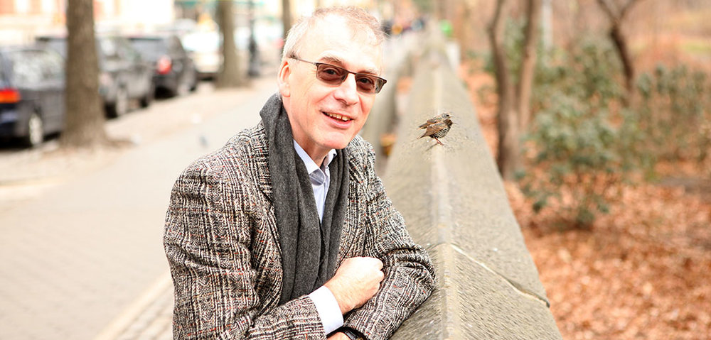 Fordham English Professor Christopher GoGwilt in Central Park with a pair of starlings (Photo by Tom Stoelker. This photo and the accompanying story--also by Tom Stoelker--originally appeared in Fordham News on January 17, 2018)
