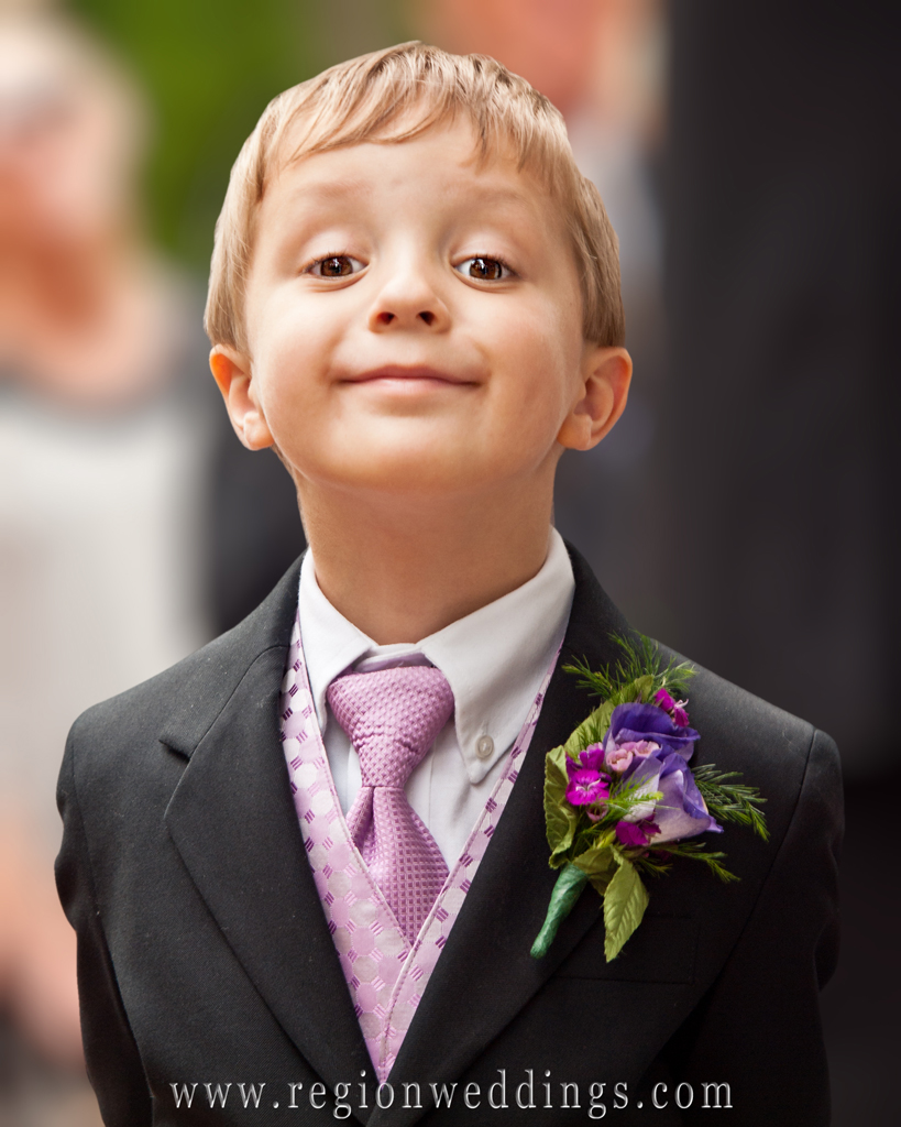 Cute ring bearer grins for the camera at an outdoor wedding at Deep River Park.