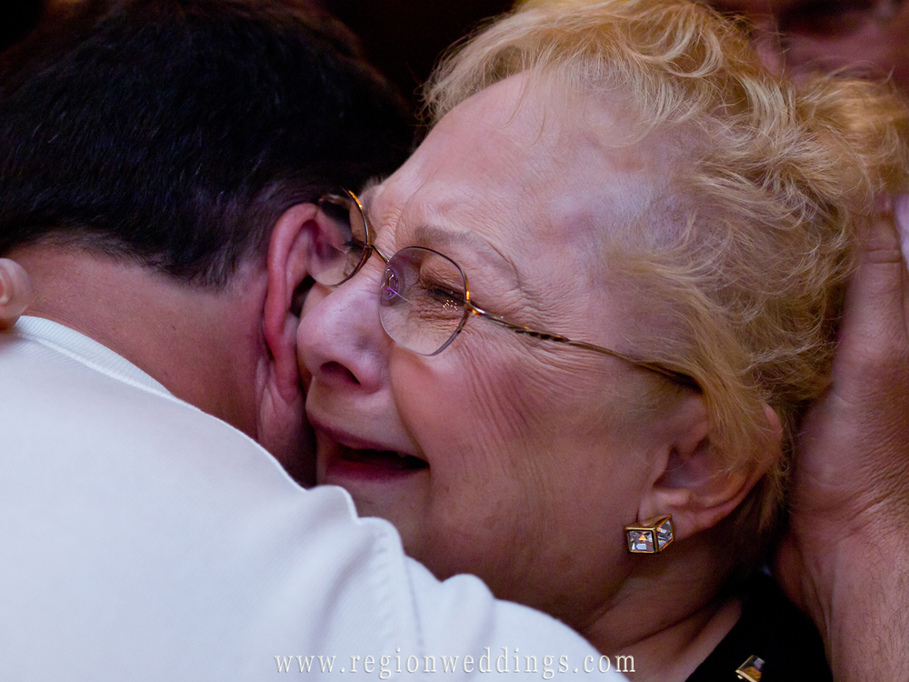 An emotional grandmother tears up as she greets family at a summer wedding reception at the old Crown Point Courthouse.