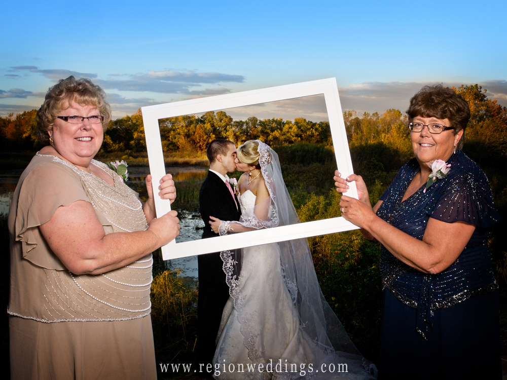 The mothers of the bride and groom pose for this fun family wedding photo while holding up a large picture frame.