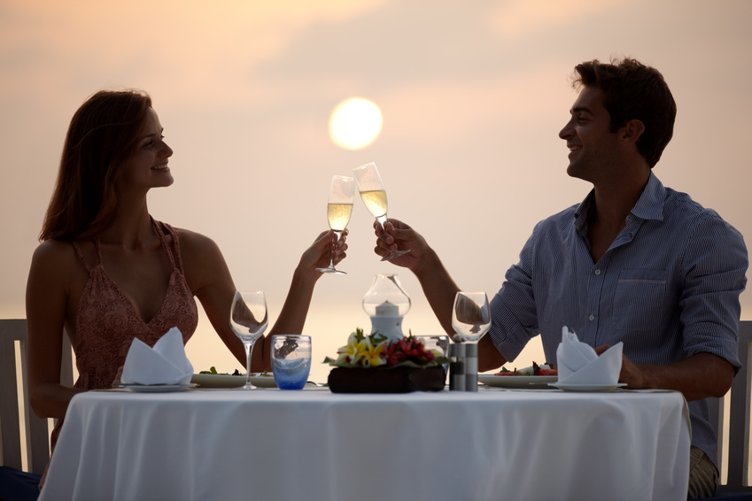 A newly married couple share a champagne toast as they dine outdoors in front of a summer sunset during their honeymoon.