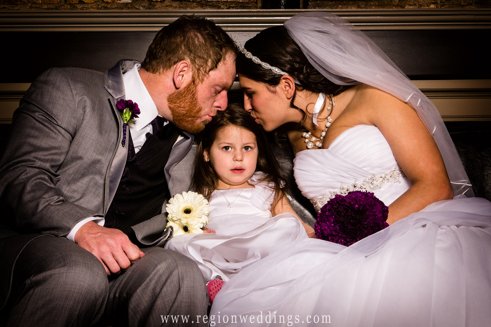 A family wedding photo captures a tender moment between bride, groom and daughter.