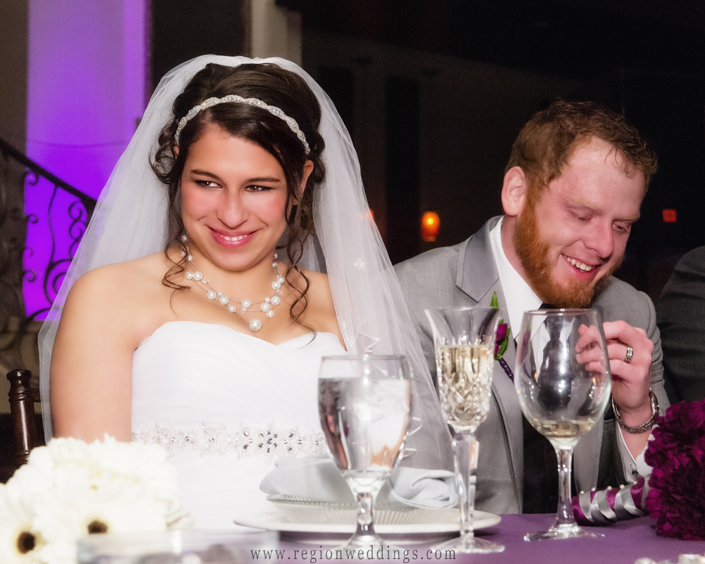 A candid picture of the bride and groom laughing during a speech from the maiden of honor.