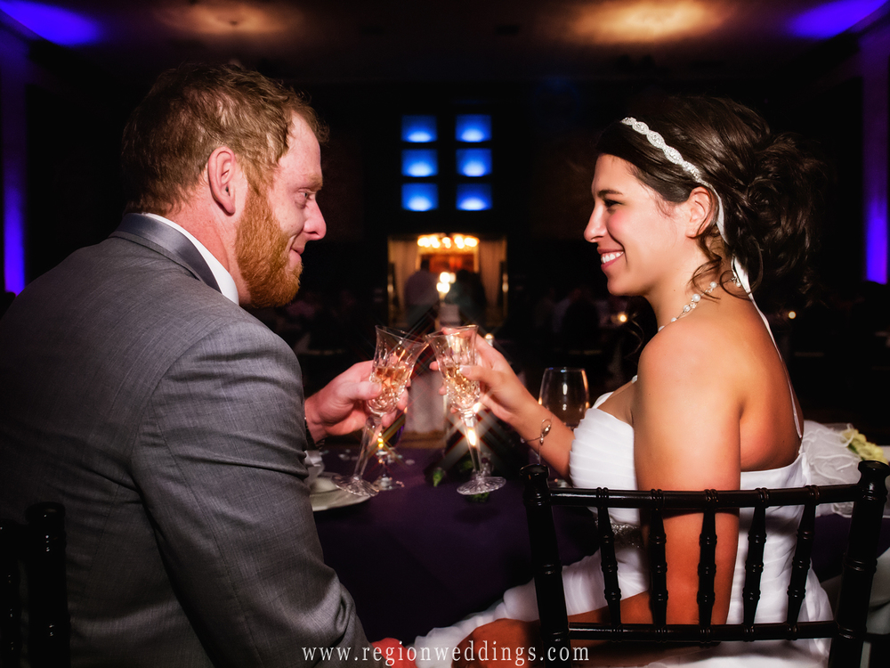Bride and groom raise their champagne glasses in a toast at the beautiful Allure ballroom in Laporte, Indiana.