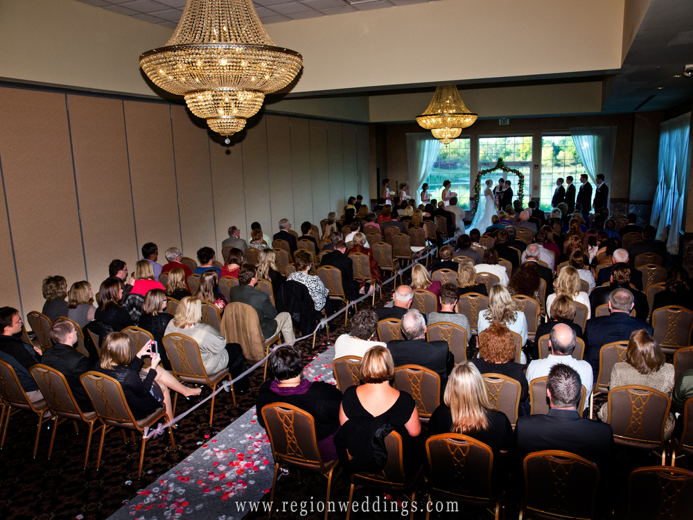 An indoor wedding ceremony takes place at Avalon Manor in Hobart, Indiana.