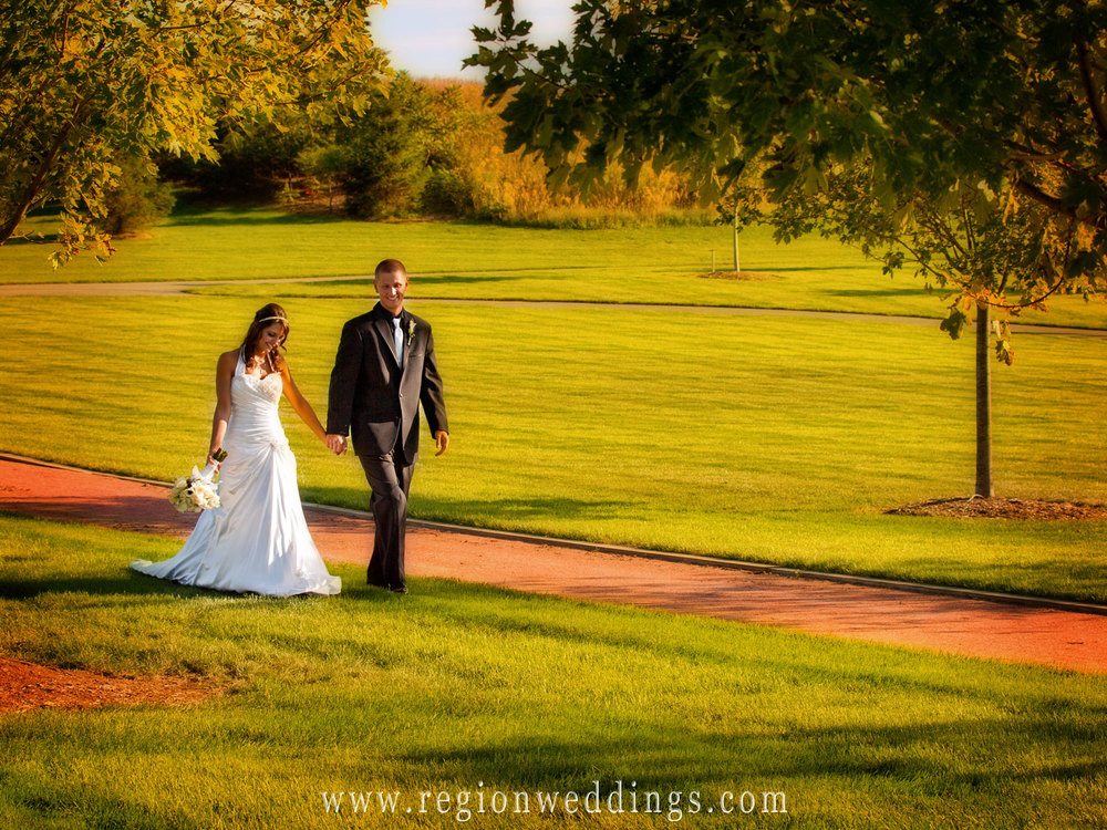 A bride and groom walk across the greenery of Centennial Park.