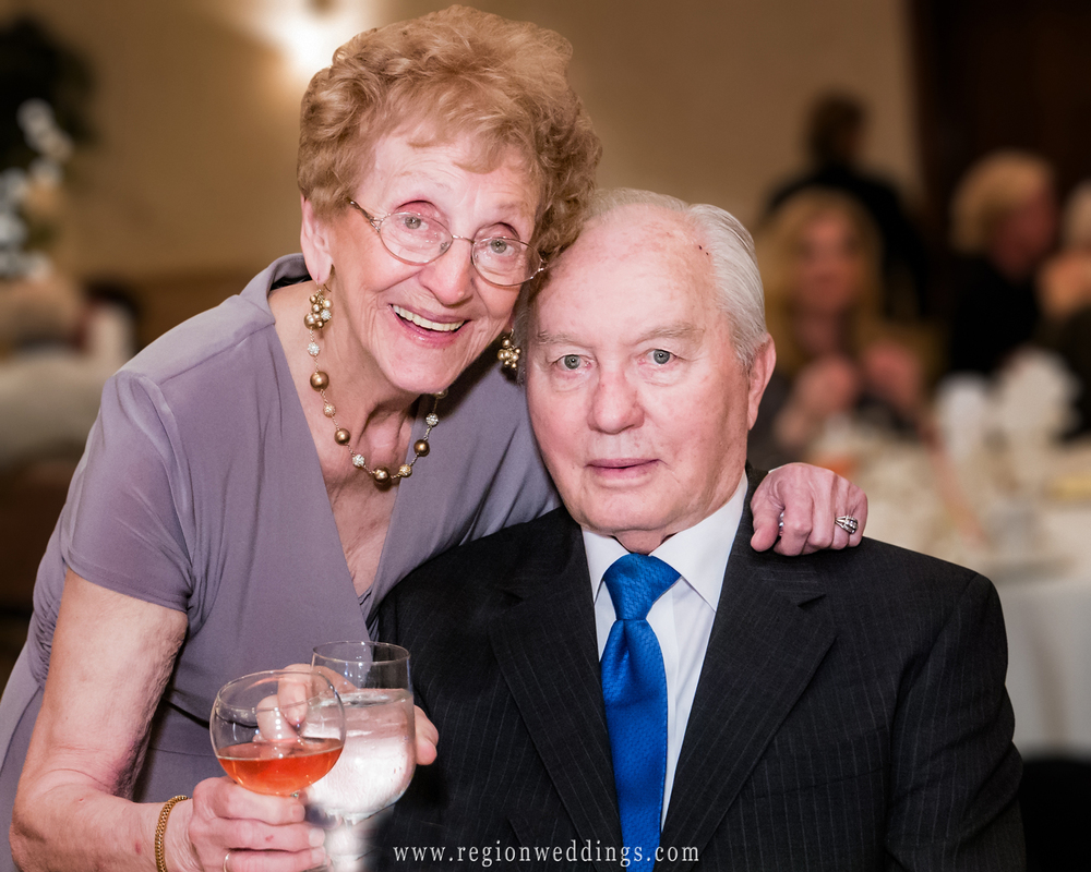 An elderly couple celebrates with a champagne toast during their celebration party.
