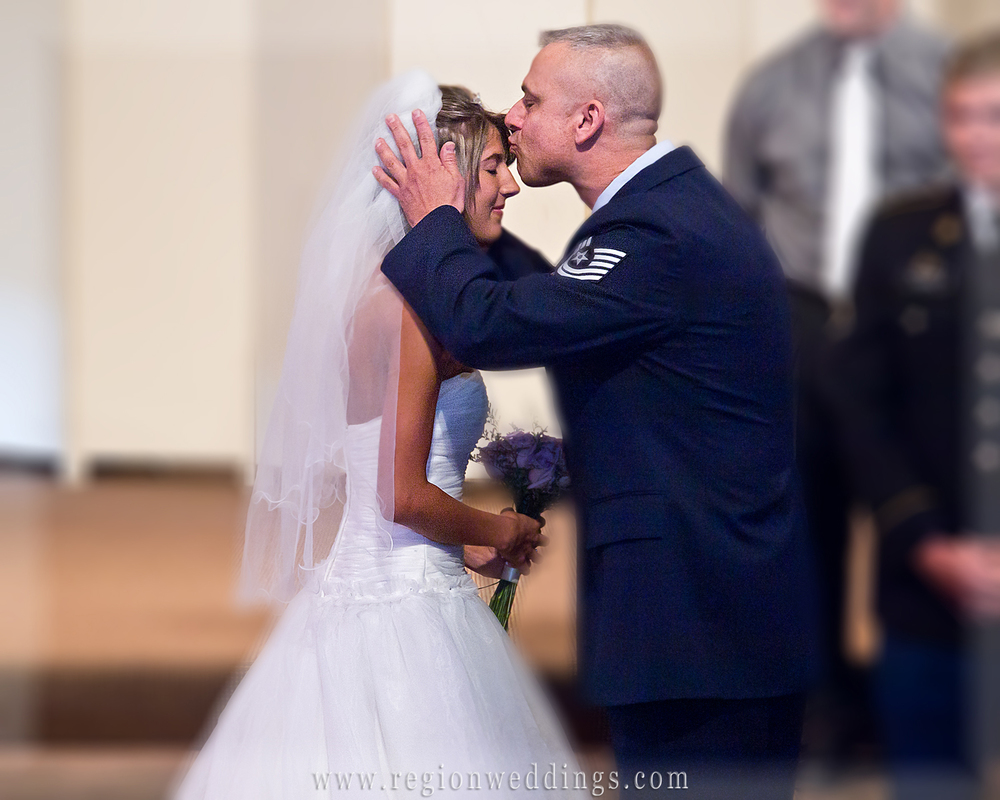 Father of the bride gives his daughter away with a kiss at a military wedding ceremony in New Buffalo, Michigan.