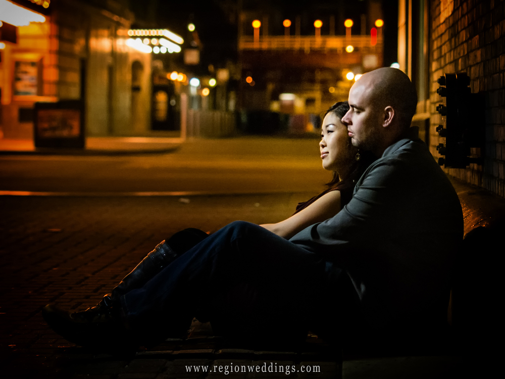 A romantic couple cuddles in a Chicago alley way at night for their engagement photos.