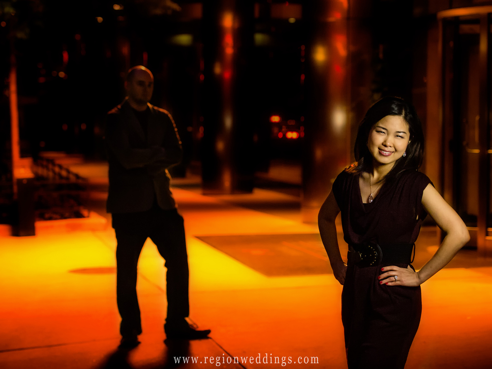 A beautiful asian woman poses for an engagement photo at a Chicago hotel entrance while her fiancé looks on in the distance.