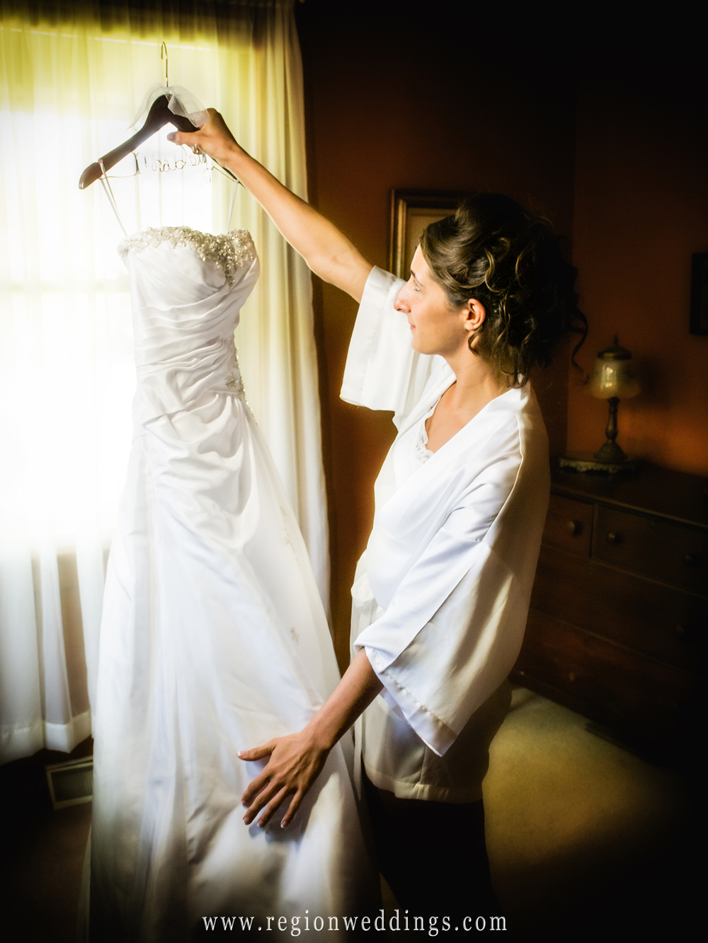 The bride admires her beautiful wedding dress on the morning of her June wedding in Homewood, Illinois.