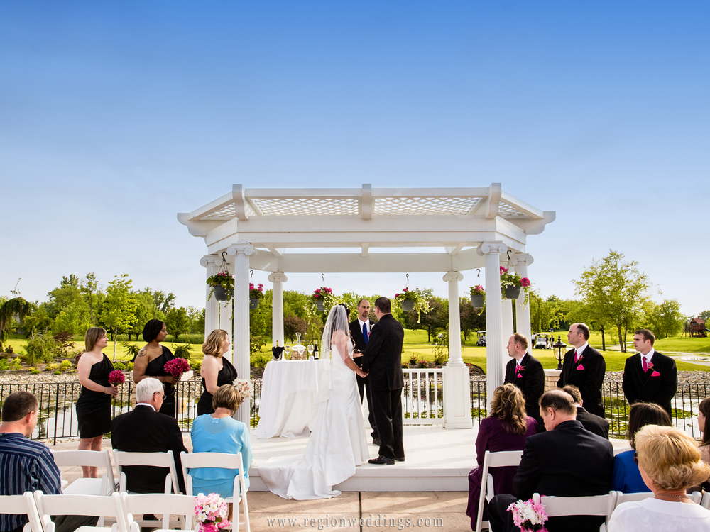 Guests look on as an outdoor wedding ceremony takes place at White Hawk Country Club in Crown Point, Indiana.