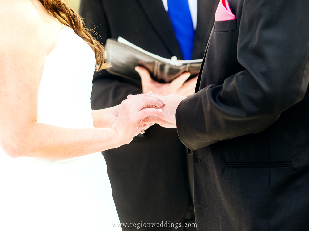The bride and groom exchange rings during their outdoor wedding ceremony in Crown Point.