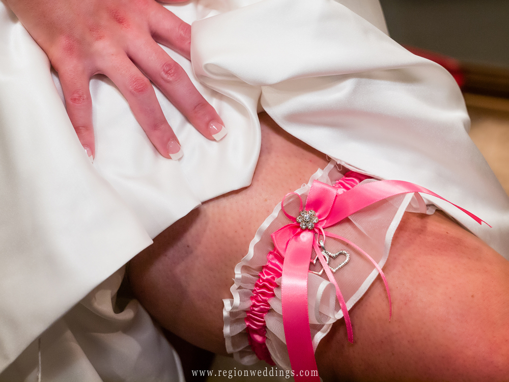 A pink garter with attached hearts is shown off on the leg of a bride.