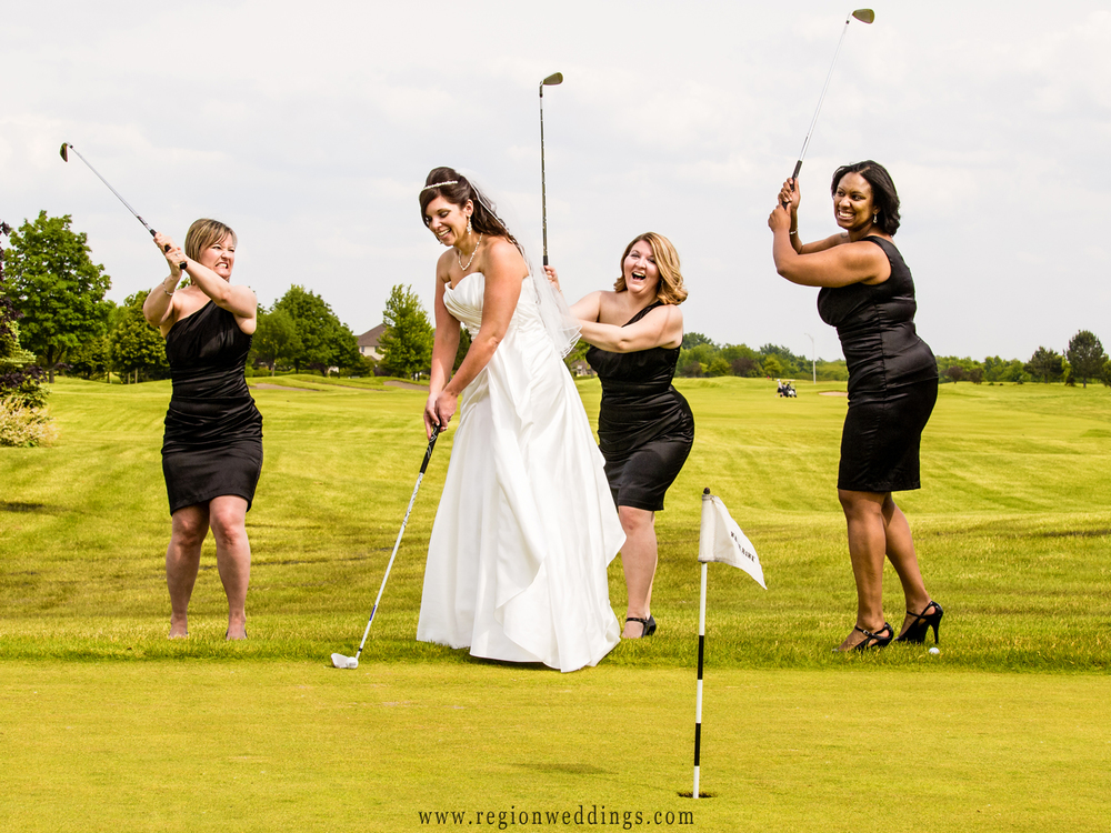 The bridesmaids attack the bride with golf clubs for this fun wedding photo at White Hawk Country Club.