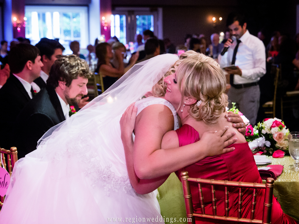 Bride and maid of honor share a tender moment at a wedding reception at Aberdeen Manor.