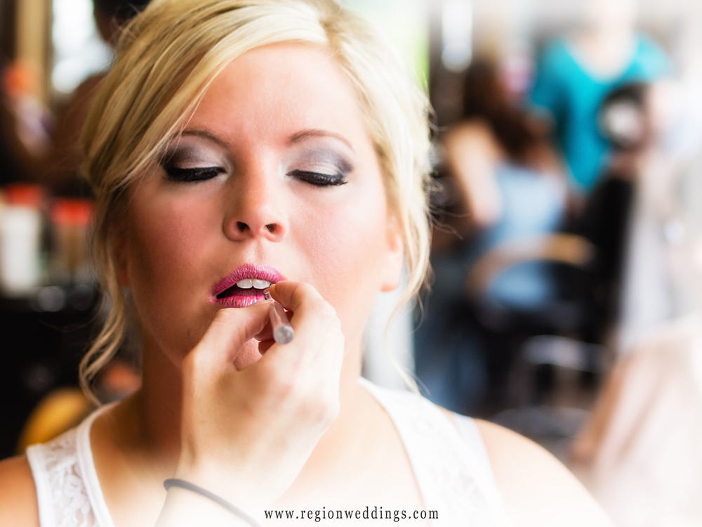 Bride has lipstick applied for her wedding day at Thomas William Salon in Crown Point, Indiana.