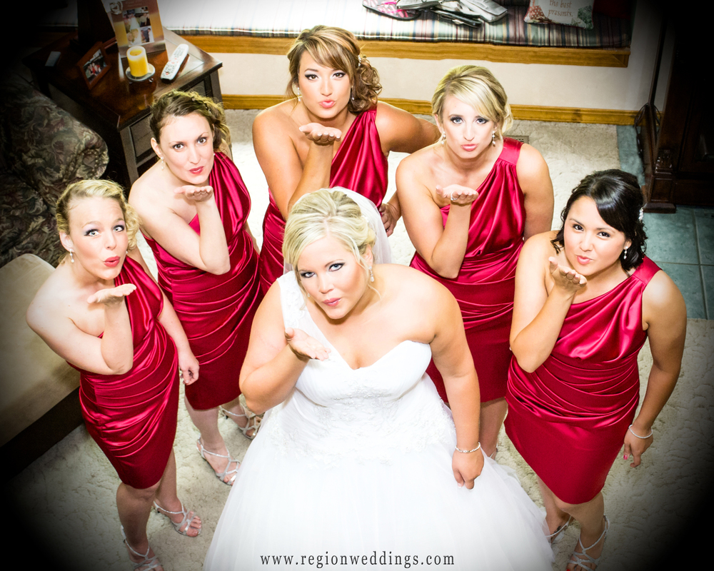 The bridesmaids blow kisses to the wedding photographer in their pink single strap bridesmaid dresses.