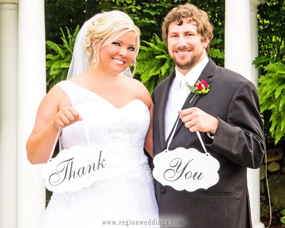 Bride and groom hold out wedding thank you signs in front of the garden gazebo at Aberdeen Manor in Valparaiso, Indiana.