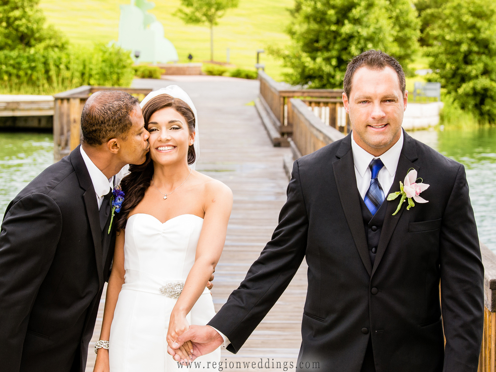 Dad kisses his daughter as he gives her to the groom on the bridge at Centennial Park in Munster, Indiana.