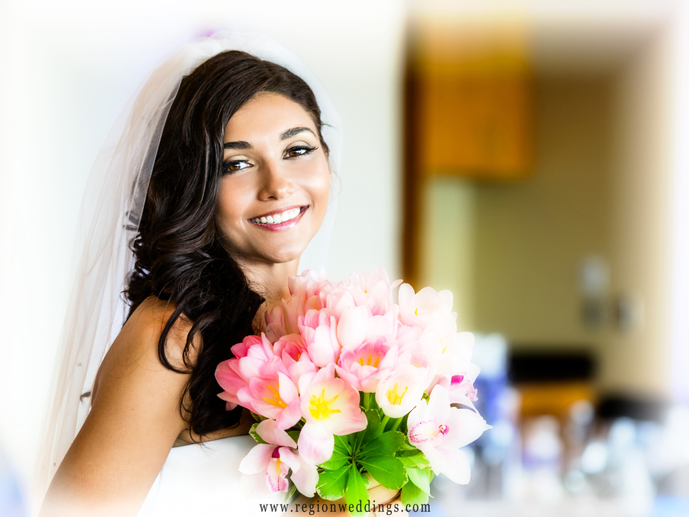 A close up portrait of the bride holding her glowing bouquet of pink flowers.