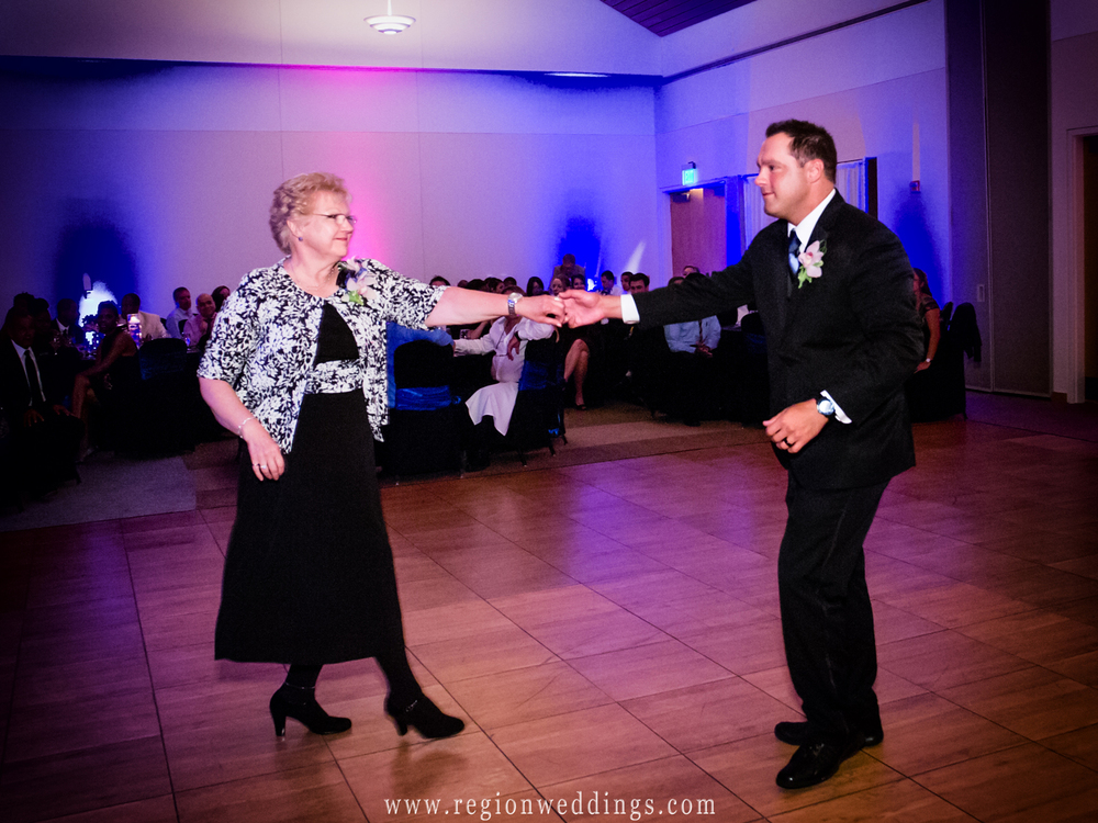 The groom ballroom dances with his mom at hgis wedding reception in Munster, Indiana.