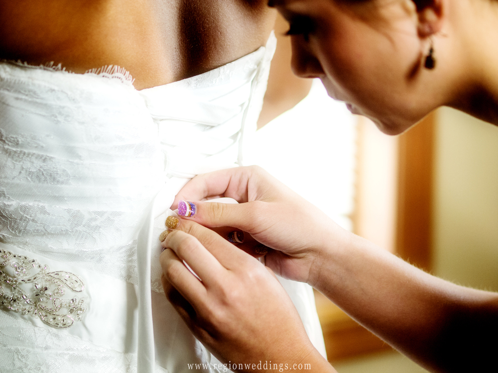 The bride's sister helps tie the wedding dress.