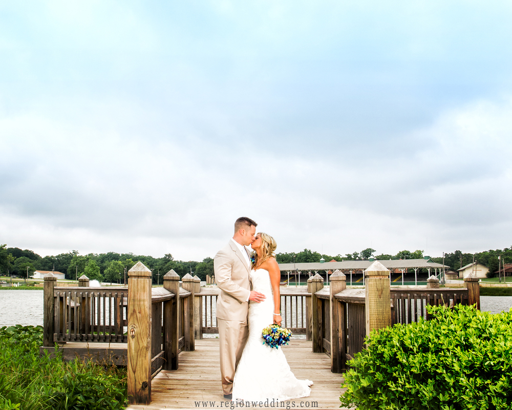 The bride and groom kiss at the edge of a pier inside the Lake County Fairgrounds.