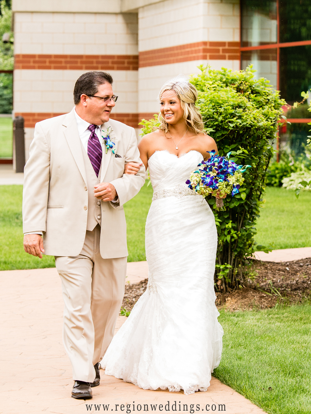 Bride walks down the aisle with her Dad at an outdoor wedding ceremony at the Halls of St. George.