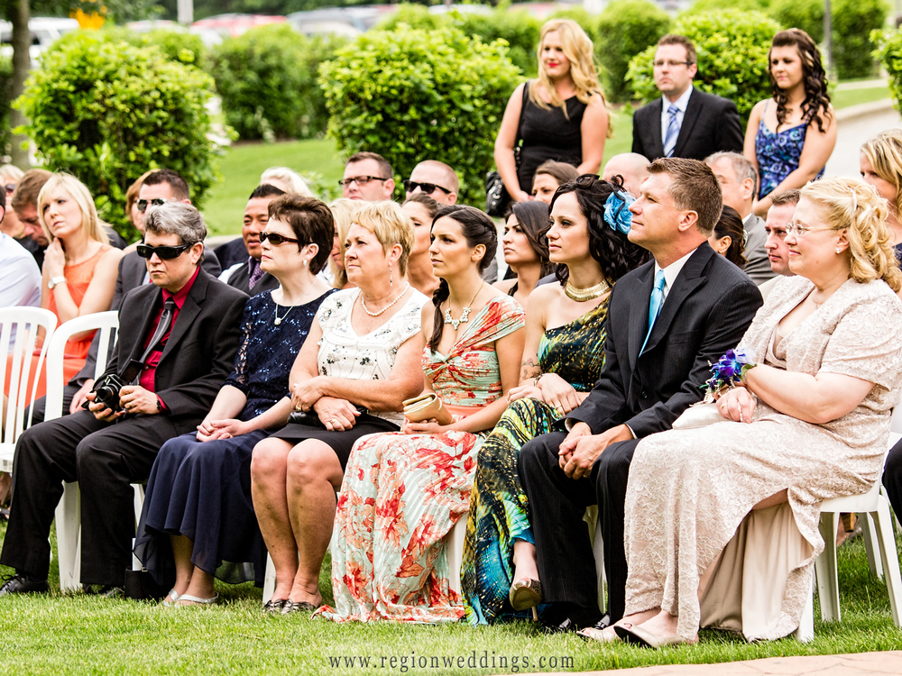 Family sits in chairs at an outdoor wedding in Schererville, Indiana.